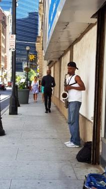 Đi ngang gặp anh jazz đang thổi kèn. Anh thổi hai giọng, một thấp to tiếng rền vang xa và giọng cao anh thổi dịu dàng thanh thoát hơn.