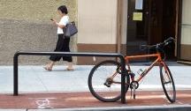 đang chụp ảnh cái xe đạp thì người đàn bà đi ngang.