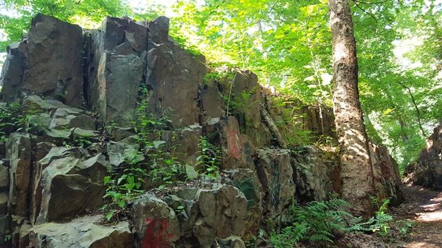Giữa rừng, bên suối, có một ngọn đồi toàn đá. Đồi toác làm hai, có đường đi chính giữa đủ rộng cho hai người (nhỏ con) đi. Vách đá khá cao, độ ba mét, dễ leo nên đã có một tên quỷ sứ phá phách nào đó leo lên vẽ bậy bằng sơn đỏ, sơn trắng.