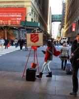 Một cô gái đang làm việc từ thiện, thu tiền cho Salvation Army. Sau lưng cô là cái cầu trên không trung, nối liền hai tòa nhà, một thứ hành lang (concourse) nối liền các tòa nhà để người ta không phải ra ngoài trời lạnh. Đây là hai tòa nhà đối diện với cửa Penn Station (trạm xe lửa tên Penn) ở New York.